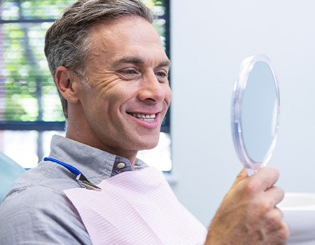 Older man looking at smile in mirror
