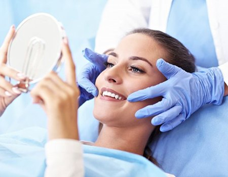 woman admiring her smile in hand mirror after cosmetic dental treatment
