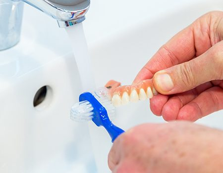 Closeup of patient brushing their dentures