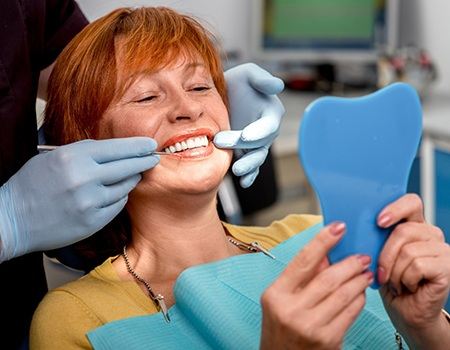 Woman smiling at reflection in dentist's office