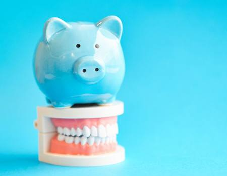 light blue piggy bank on top of a set of dentures