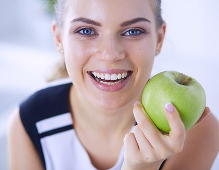 Woman with a healthy smile holding an apple.