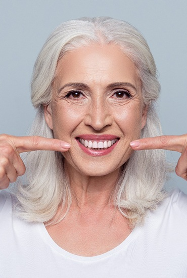 Older woman with dental implants pointing to her smile.